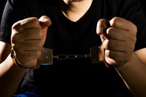 Man in black shirt in handcuffs