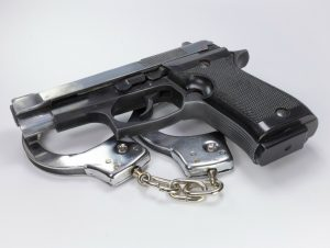 Gun and handcuffs on white background