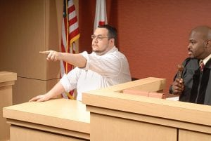 man pointing at someone in courtroom